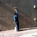 Un señor repara la pared que le rayaron